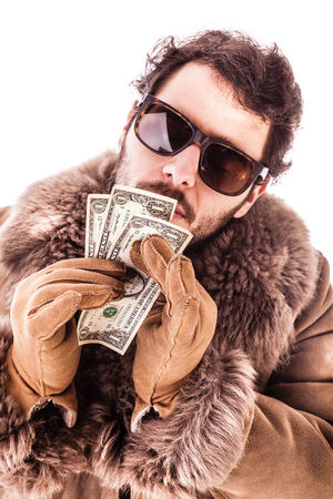 obsessed: a young man wearing a sheepskin coat isolated over a white background holding banknotes Stock Photo