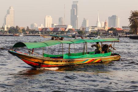 phraya: a thai longtail boat and the bangkok skyline seen from the Chao Phraya river