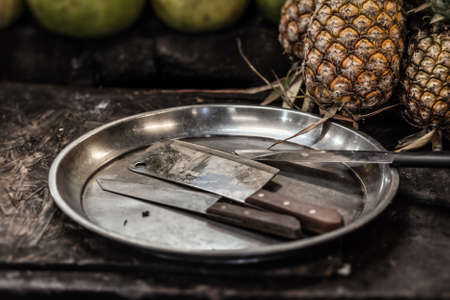 grunge flatware: a chopper an two knives on a steel tray near some ananas
