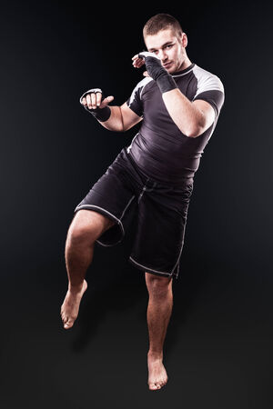 kickboxer: a young kickboxer or boxer posing over a dark background Stock Photo