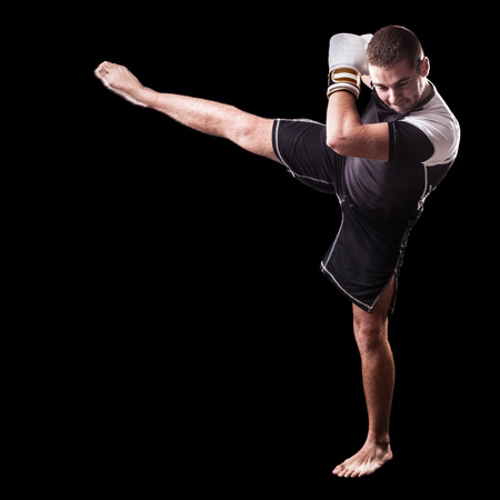 thai arts: a young kickboxer or boxer isolated over a black background
