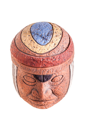indian artifacts: a terracotta olmec face idol souvenir isolated over a white background
