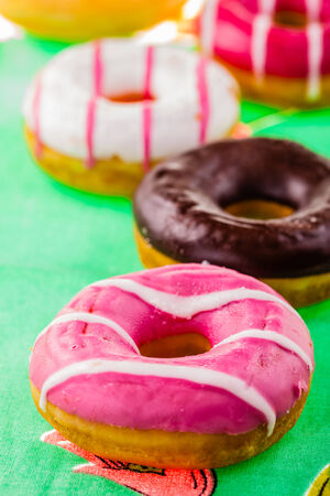ornated: some delicious and colorful donuts on a green ornated tablecloth