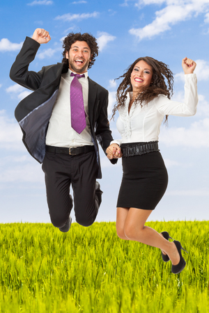 An handsome businessman and a gorgeous businesswoman jumping over green meadow photo