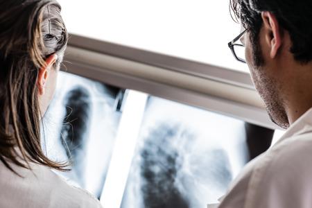dos médicos yound que examinan una película de rayos X en el diafanoscopio Foto de archivo