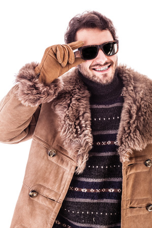 a cheerful young man wearing an expensive sheepskin furry coat isolated over a white background and raising his sunglasses Stock Photo