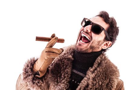 un homme jeune et riche vêtu d'un manteau en peau de mouton isolé sur un fond blanc tenant un cigare