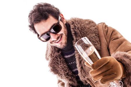 snobby: un giovane uomo che indossa un cappotto di pelle di pecora isolato su uno sfondo bianco in possesso di un sigaro e un bicchiere di champagne Archivio Fotografico