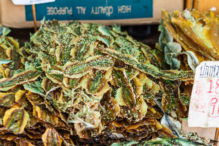 Dry Fish (Yellow Stripe Trevally) coated with sesame on sale in a thai street market photo
