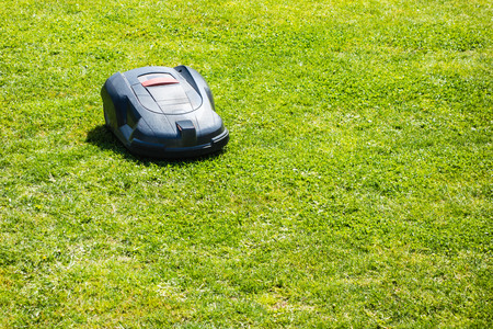 a robotic lawn mower working on a green grass field photo