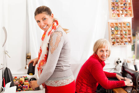 two happy seamstresses working in a taylor shop photo