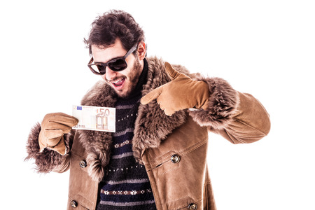 a young man wearing a sheepskin coat isolated over a white background holding banknotes photo