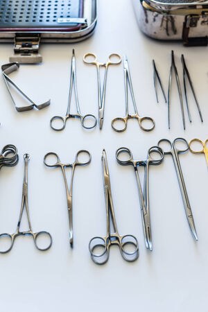 surgical instruments and tools including scalpels, forceps and tweezers arranged on a table for a surgery photo