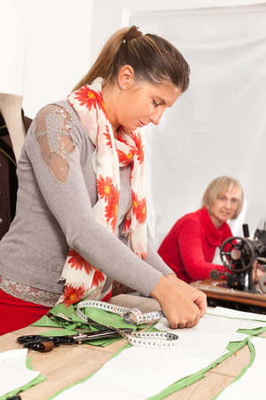 taylor: two happy seamstresses working in a taylor shop