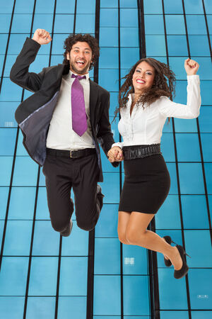 An handsome businessman and a gorgeous businesswoman jumping over a skyscraper photo