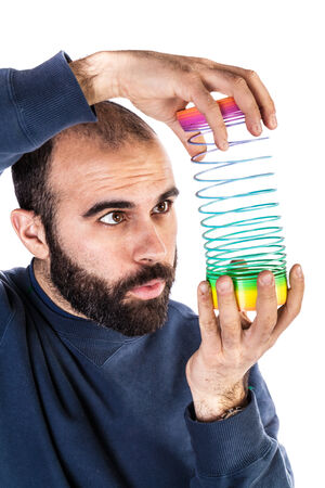 slinky: a bearded man playing with a rainbow slinky toy and looking silly