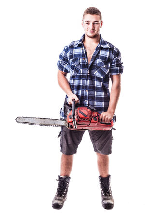 petrol powered: a young lumberjack wearing a checkered shirt and holding a chainsaw isolated over white background