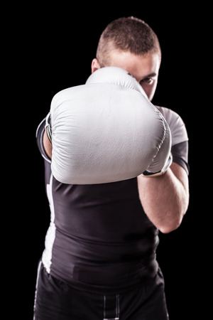 kickboxing: a young kickboxer or boxer isolated over a black background