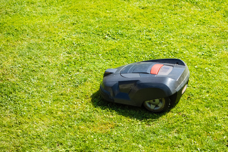 a robotic lawn mower working on a green grass field Stock Photo