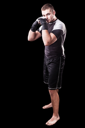 a young kickboxer or boxer isolated over a black background