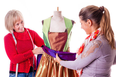 customer tailor: two happy seamstresses working on a dress on a mannequin isolated over a white background