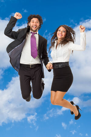 An handsome businessman and a gorgeous businesswoman jumping over a blue sky photo