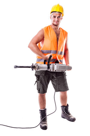 a young road worker wearing a hardhat and a visibility vest holding a jackhammer isolated over white background Stock Photo