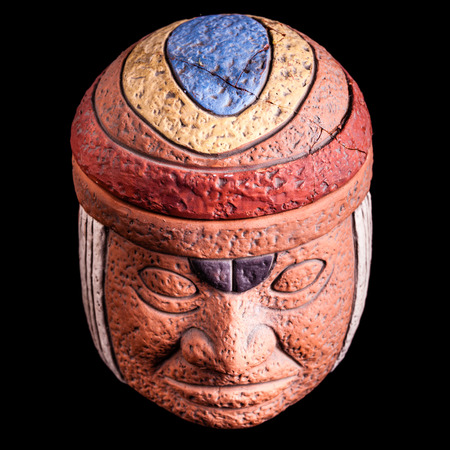 indian artifacts: a terracotta olmec face idol souvenir isolated over a black background