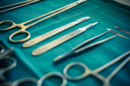 plastics: surgical instruments and tools including scalpels, forceps and tweezers arranged on a table for a surgery