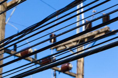 over voltage: close up shot of some high voltage electricity cables over the blue sky Stock Photo