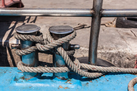 close up shot of a big bollard with a rope tied to it photo