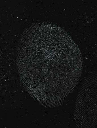 labyrinthine: Macro shot of a human thumb fingerprint over a black background