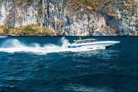 a speed boat passing near a cliff in Phi Phi Island, Thailand photo