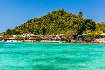 a tropical island in Thailand vith a vibrant azure sea photo