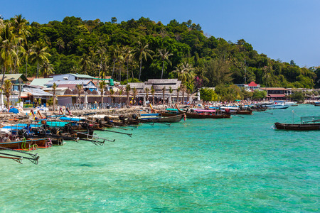 the main pier of the tropical thai island named Phi Phi, with a lot of colorful longtail boats photo