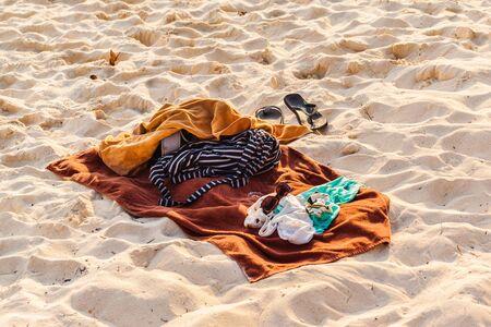 belongings: a beach towel with some personal belongings on a tropical beach Stock Photo