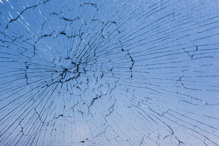 macro shot of a broken glass window against the blue sky