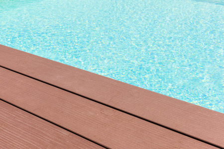 wooden planks at the pool side with vibrant pool water