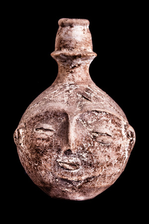 anthropomorphous: an ancient terracotta vase or jug shaped like a human face isolated over a black background