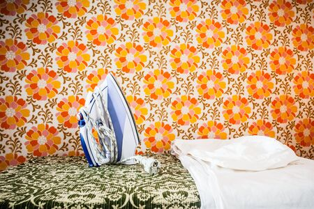 launderette: an iron appliance over a wall covered with retro styled floral wallpaper