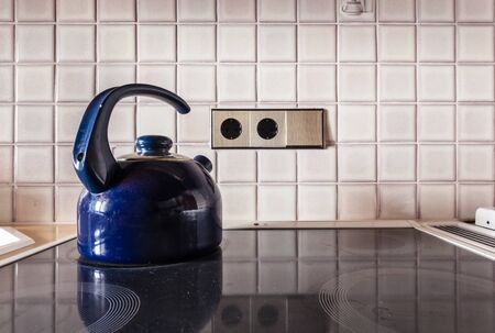 tiled stove: a blue metal kettle on the cooker of an electric stove in a kitchen
