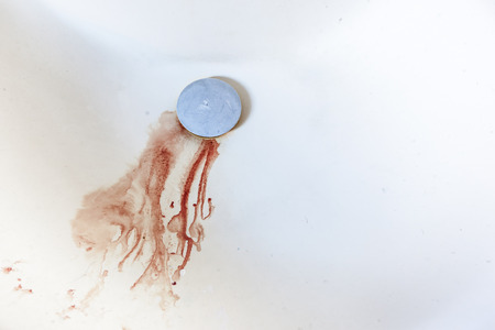 blood droplets going down the drain in a domestic sink