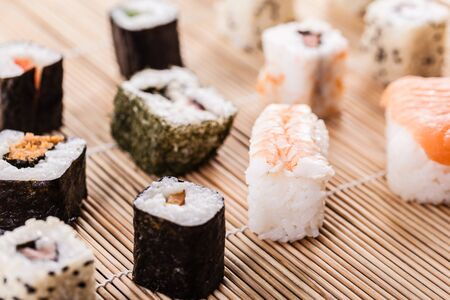 sushi set: an assortment of different sushi pieces on a wooden bamboo sushi mat in a japanese restaurant