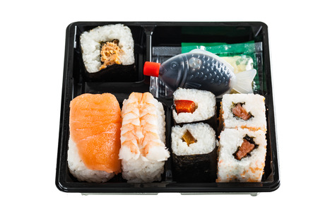a sushi box or bento box with assorted sushi pieces isolated over a white background