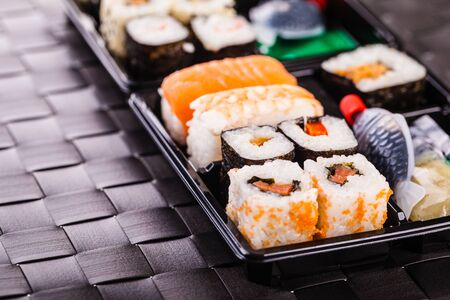 lunch tray: a sushi box or bento box with assorted sushi pieces over a dark black lunch mat