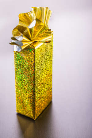 wrapped gift: a golden wrapped gift box on a dark wooden surface