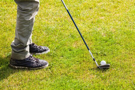golf swing: detail of a driver club and a golf ball on a golf course