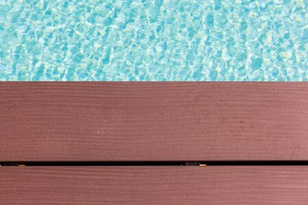 pool side: wooden planks at the pool side with vibrant pool water