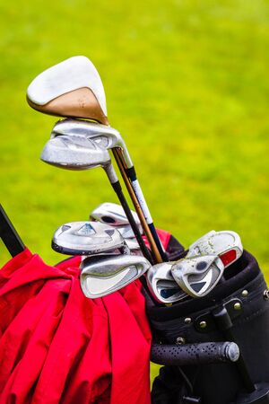 caddie: a wheeled golf bag full of golf clubs of a vibrant golf course