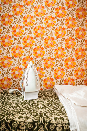 tacky: an iron appliance over a wall covered with retro styled floral wallpaper
